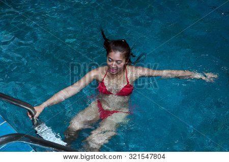 Pretty Asian Woman Wearing Red Bikini Swimming At Swimming Pool And Enjoying Travel On Vacation Summ