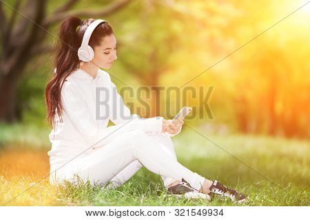 Happy woman with headphones relaxing in the sunny park. Beauty nature scene with colorful background. Fashion woman enjoying the music from her mobile phone in fall season. Autumn outdoor lifestyle