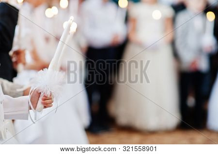 Young Girl In White Hold Candle In Hand At First Holy Communion.