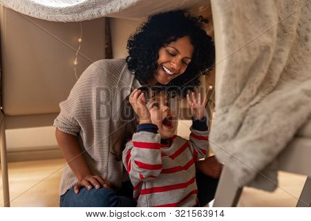 Mother And Her Little Daughter Playing In A Blanket Fort