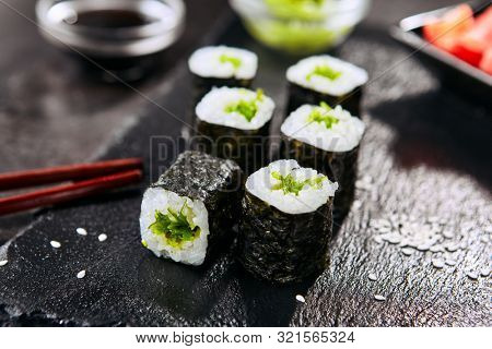 Macro shot of seaweed hosomaki sushi on natural black slate plate background with selective focus. Thin small maki sushi rolls with rice, wakame, kelp salad or chuka and nori closeup
