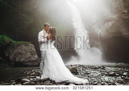 Young Couple In Love Bride And Groom, Wedding Day Near A Mountain Waterfall. Enjoy A Moment Of Happi
