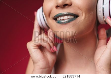 Cropped image of joyful punk girl with bizarre hairstyle and dark lipstick smiling while listening to music with headphones isolated over red background poster