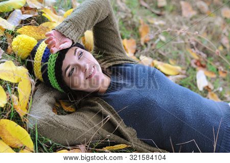 Smiling woman portrait dressed in beanie hat with pom pom, outdoor in autumn park