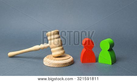 Two Figures Of People Opponents Stand Near The Judge's Gavel. The Judicial System. Conflict Resoluti