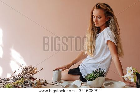 Young Female Ceramist Sitting On Table In Her Small Studio