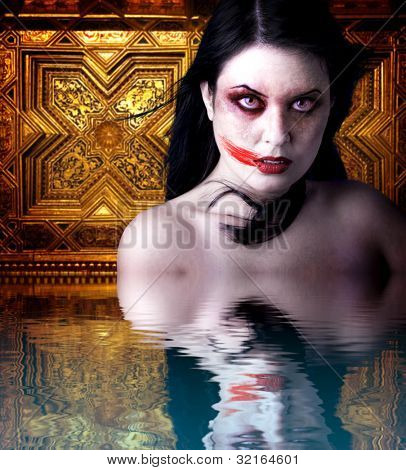 Woman vampire with blood in his mouth. Gothic Image halloween over gold background  in the water reflection