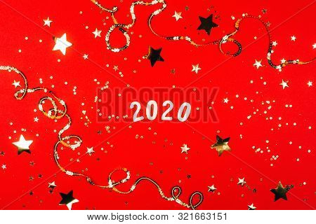 2020 On Silver Sparkles And Red Background. Flat Lay Style.