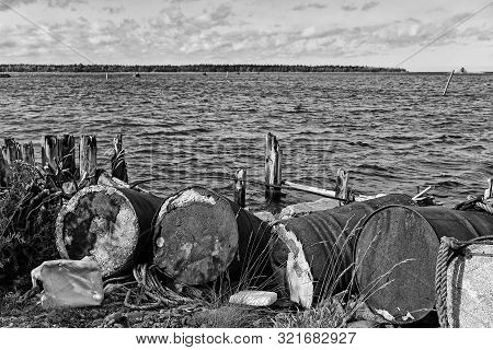 Old Barrels Have Been Left To Rot By The Remains Of An Old Wooden Pier At The Fishing Harbour Of Kal