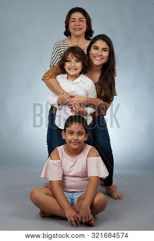 Portrait Of Happy Hispanic Grandma And Kids On Gray Studio Background