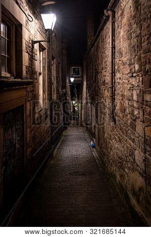 A Dark Creepy Narrow European Alley At Night, Surrounded By Bricks And Cobblestone. Illuminated Only