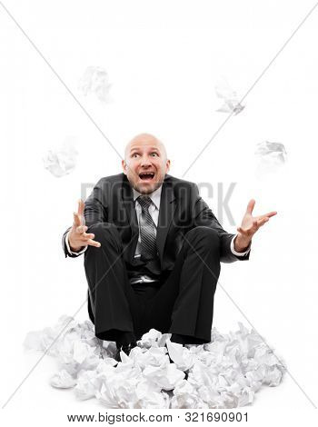 Business problems and failure at work concept - unhappy tired or stressed businessman in depression sitting down floor hand throwing crumpled torn paper document white isolated