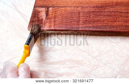 Close Up Hand Use Brush Paint Clear Lacquer On The Wood Surface. Hands Are Protected By Gloves. Fini