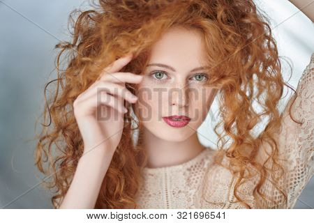 Beautiful young woman with long red hair. Hair care, hair coloring.