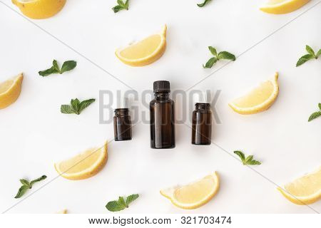 Three Bottles Of Essential Oil Surounded With Fresh Herbal Green Mint Leaves And Lemon Lobules. Flat