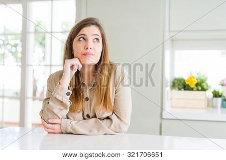 Beautiful young woman at home with hand on chin thinking about question, pensive expression. Smiling with thoughtful face. Doubt concept.