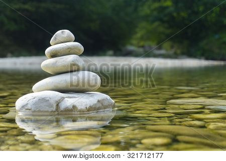 Harmony, Balance And Simplicity Concept. A Stone Pyramid On The Background Of River Water. Simple Po