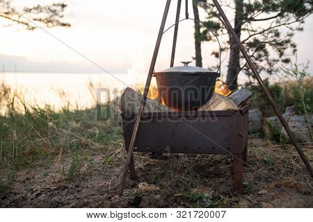 Hiking Pot In The Bonfire. Traveling In The Mountains With Tents