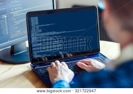 Back View Of Man Freelancer Is Working On Laptop At Home Office. Programmer Developer Is Writing Pro