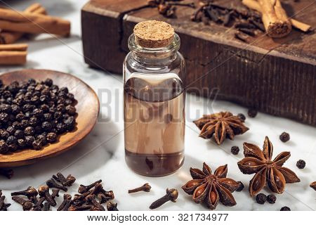 Aromatic Seeds Essential Oil On Glass Bottle. Cinamon, Anise, Peppercorn, Clove Oil For Weelness, Sp