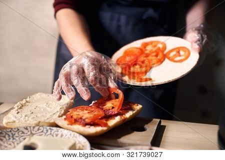 Chef Mastery Hands Holding White Plate With Slices Of Cheese And Sausage. Putting Pieces Of Tomato O