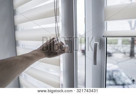 Man Holding Window Handle On A Plastic Window With White Fabric Roller Blinds In The Living Room. Cl