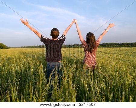 Young Couple In Field Holding Hands Up