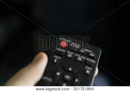 poster of Close up on a mans hand with the remote control want switch on the TV and presses the button on the remote control. Remote control in hand closeup.