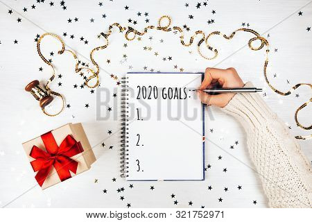 Holiday Decorations And Notebook With Wish List On White Rustic Table, Flat Lay Style. Planning Conc