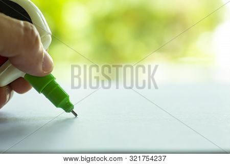 Woman's Holding Green Liquid Correction Writing Pen Or Liquid Paper For Correct Hand Writing Mistake
