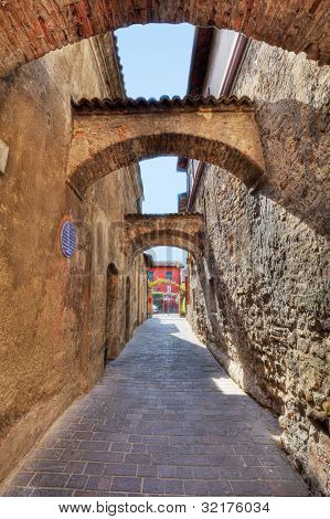 Vertical oriented image of arched pathway among ancient brick walls in Sirmione, Northern Italy.