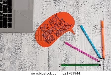 Handwriting text writing Do Not Reinvent The Wheel. Concept meaning stop duplicating a basic method previously done Open laptop blank speech bubble pens ballpoints lying vintage wooden table. poster