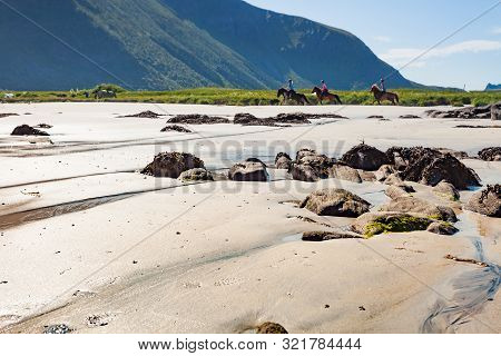 Scenic Sea Coast With People Riding On Horse Back At Gimsoysand Sandy Beach. Nordland County, Lofote