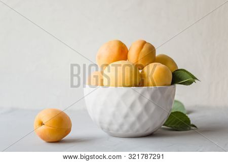 Fresh Ripe Apricots In A White Plate On A Gray Background. The Concept Of Proper And Delicious Food.