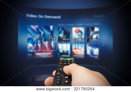 Vod Service Screen With Remote Control In Hand. Video On Demand Television Internet Stream Multimedi