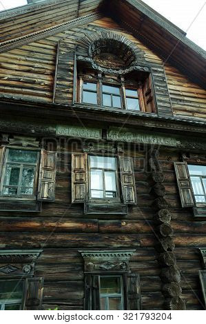 Very Old Log House With Three Floors. Shutters On The Windows, Wood Carving, Museum Of Wooden Archit