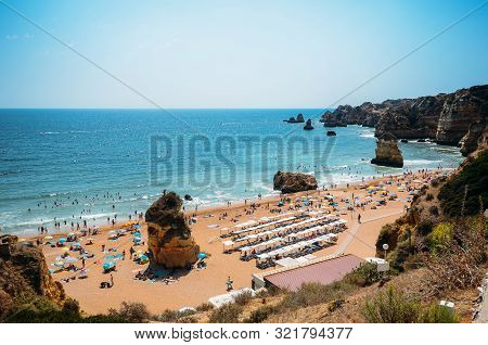 High Perspective View Of Beachgoers At Cova Redonda Beach In Algarve, Southern Portugal On A Summer