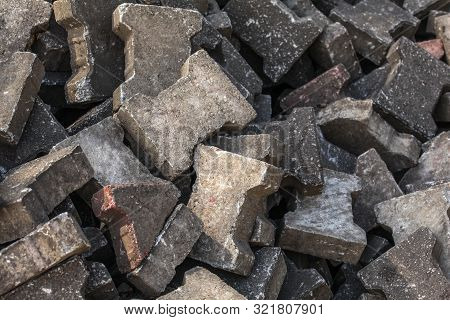 Pile of old discarded pavement (segmental paver) cobble stones. poster