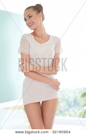 Beautiful sensual woman in very short miniskirt posing sideways to camera against a high key background