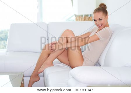 Sideview of beautiful introspective woman in skimpy outfit sitting on a white sofa with her bare feet up on the coffee table