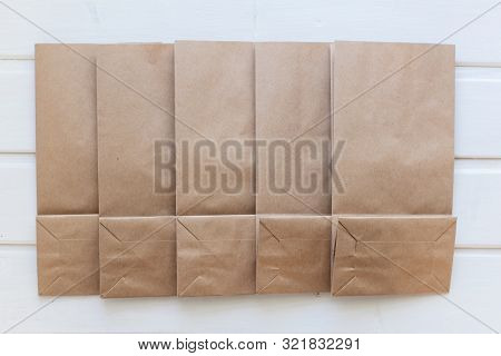 Paper Bags On Light Wooden Floor. Simple Brown Paper Bags For Lunch Or Meal. The Layout For The Desi