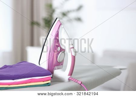 Modern Electric Iron And Clean Folded Clothes On Board In Room. Space For Text