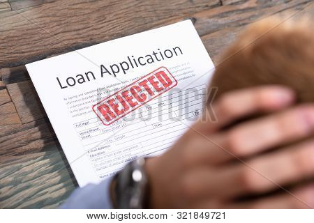 Stressed Person Looking At Rejected Loan Application