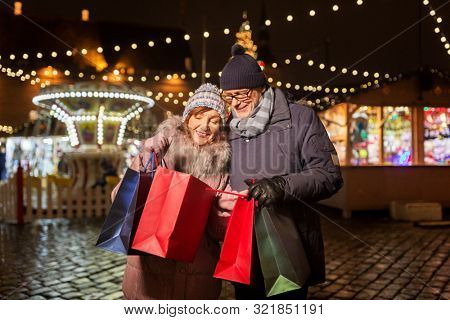 poster of sale, winter holidays and people concept - happy senior couple with shopping bags at christmas market souvenir shop on town hall square in tallinn, estonia
