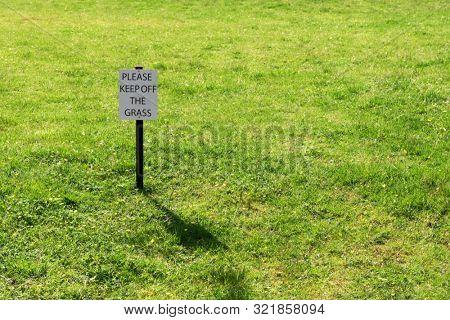 Keep off grass sign on a green backyard lawn meadow park
