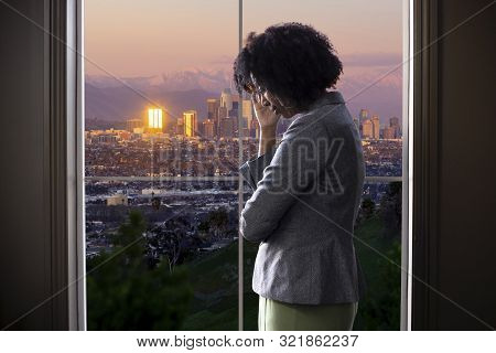 Black Female Businesswoman Looking Worried Or Tired By An Office Window With A View Of Downtown Los