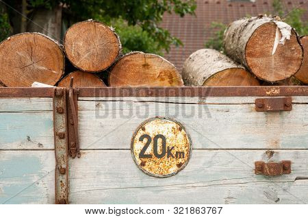 Rusty Old Sign On Agricultural Trailer With Wood As Cargo, Speed Restriction To 20 Km Per Hour