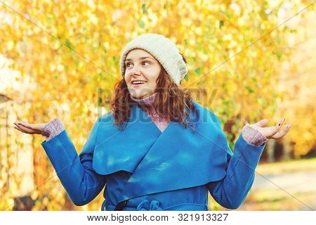 Smiling Girl Wearing Autumn Coat, Knitted Hat Outdoors. Woman Walking At Autumn Park. Autumn Fashion
