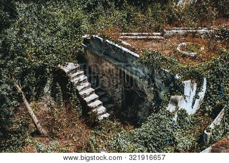 Desolate Stony Ancient Ruins Outdoors Overgrown With Greenery And Ivy: Old Stair, Door Hole, And Bui