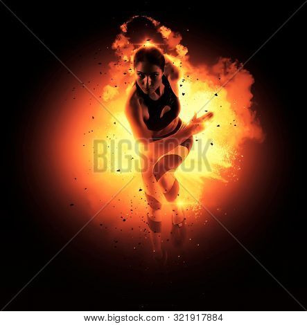Sporty young woman running on fire background